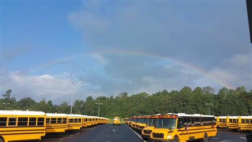 Bus parking lot with rainbow above